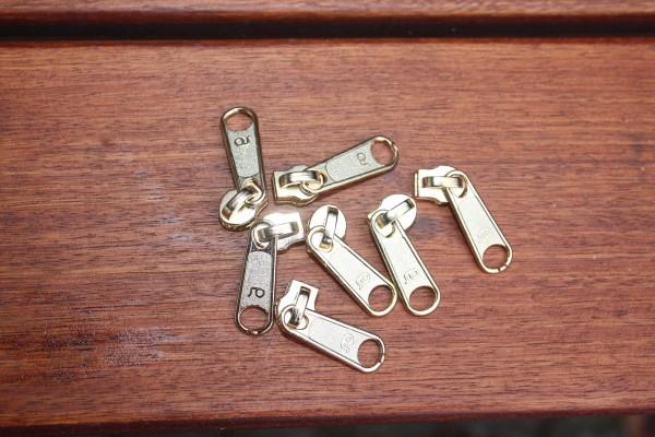 Bügelschieber für metallisierte Reißverschlussmeterware breit gold